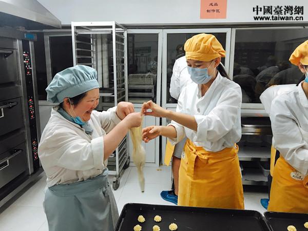 """""""喜憨儿""""慧慧(左一)在帮助实习生魏曼芯(左二)调整工具,齐心协作,挤出的曲奇饼干形状标准,精致均匀。"""